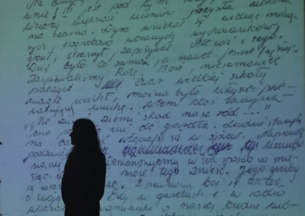 performer silhouetted against a projection of hand-written Polish text.